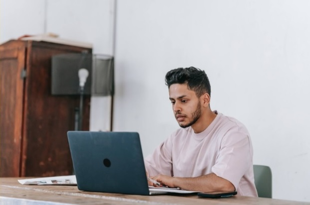 person sitting down look at a laptop